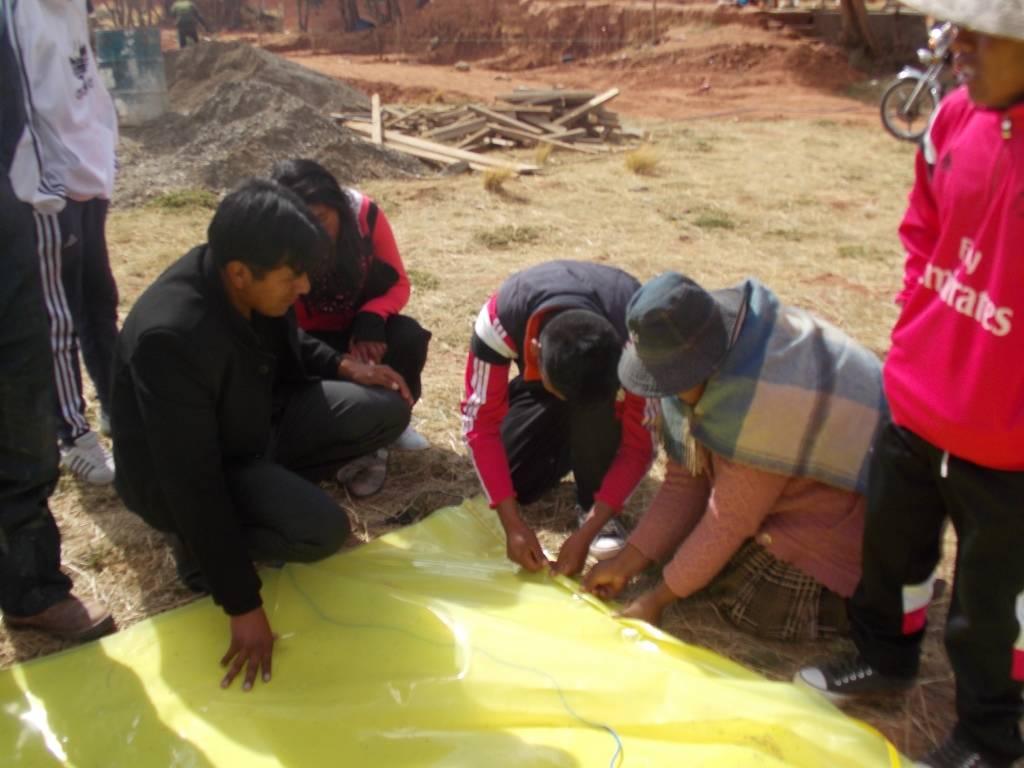 Costura de agrofilm para techado de la carpa solar del colegio, por parte de profesores, estudiantes y padres de familia